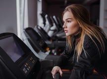 Uma opinião lateral a moça ou a mulher que fazem o cardio- exercício em um gym foto de stock royalty free
