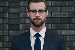Uma opinião segura o líder Um homem de negócios novo nos vidros e com uma barba olha diretamente em você fotos de stock