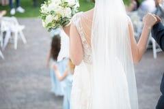 Uma opinião traseira uma noiva que guarda um ramalhete fotos de stock royalty free