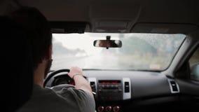 Uma opinião traseira um homem que conduz um carro na chuva Mãos em um volante, trabalho dos limpadores filme