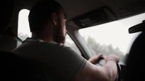 Uma opinião traseira um homem que conduz um carro na chuva Mãos em um volante, trabalho dos limpadores vídeos de arquivo