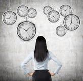Uma opinião traseira uma senhora moreno do negócio que esteja olhando os relógios de bolso pairando no ar Um conceito de um valor Fotos de Stock