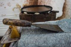 Uma pá de pedreiro suja para a cera de limpeza das sobras na bandeja grande Pekalongan recolhido foto Indonésia Fotografia de Stock Royalty Free