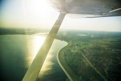 Uma paisagem aero bonita que olha fora de uma janela plana pequena sob a asa Riga, Letónia, Europa no verão Voo autêntico ex imagem de stock
