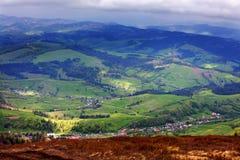 Uma paisagem bonita da montanha na perspectiva de uma vila no vale e em uma caminhada à montanha Imagem de Stock