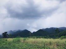 Uma paisagem bonita do campo de grama entre a montanha no dia chuvoso em Kanchanaburi, Tailândia Fotos de Stock