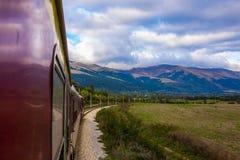 Uma paisagem da montanha, um céu bonito com nuvens brancas e grama verde, fotografada no movimento por um trem Fotos de Stock