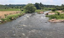 Uma paisagem do rio pequeno com montes imagem de stock