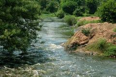 Uma paisagem do rio pequeno com rochas e árvores imagem de stock royalty free