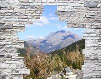 Uma paisagem em um indicador atrás de uma parede de pedra Fotografia de Stock