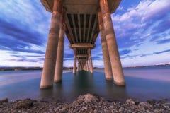Uma paisagem longa da exposição do por do sol ardente bonito sob a ponte Fotografia de Stock