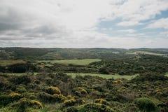 Uma paisagem natural bonita com árvores verdes em um terreno montanhoso contra um céu azul fotos de stock