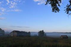 Uma paisagem pequena da vila na névoa Fotos de Stock