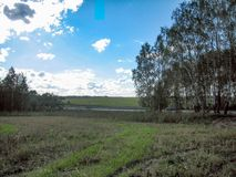 Uma paisagem rural maçante com um campo, as árvores e uma estrada em um dia ensolarado brilhante imagem de stock