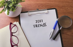 Uma palavra de 2017 tendências no papel com vidro ballpen e planta verde Imagens de Stock Royalty Free