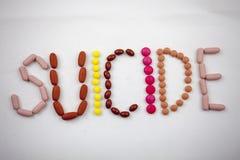 Uma palavra do suicídio, escrevendo no fundo branco em comprimidos fotografia de stock royalty free