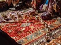 Uma parada de camelos minúsculos em um semi-círculo em um tapete persa com tapeçaria e os tamboretes taspestry atrás foto de stock