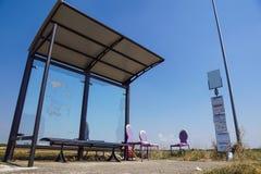 Uma parada do ônibus rural ao lado dos campos e de dano velho da cadeira imagens de stock royalty free