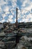 Uma parede da pedra cinzenta cobriu com arame farpado imagem de stock