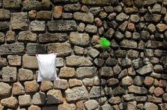 Uma parede de pedra com vassoura verde e a fronha de almofada branca que seguram na corda em Porto fotos de stock royalty free