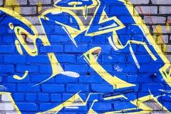 Uma parede destruída com arte dos grafittis da rua fotografia de stock