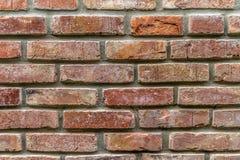 Uma parede velha de tijolos restaurados com uma cor vermelha fortemente desvanecida e umas junções desiguais imagens de stock