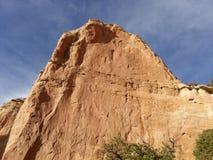Uma parede vermelha da rocha e um céu azul Imagem de Stock