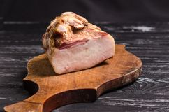 Uma parte de bacon fumado em uma placa de corte de madeira U tradicional imagens de stock