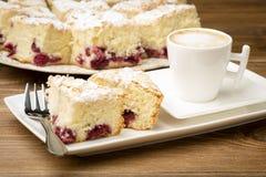 Uma parte de biscoito com cereja e uma xícara de café na superfície de madeira Fotografia de Stock Royalty Free