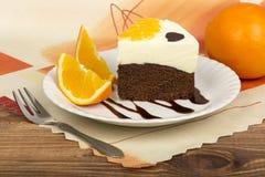 Uma parte de bolo da brownie com creme e laranjas Foto de Stock
