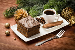 Uma parte de bolo do pão-de-espécie do Natal na placa branca na tabela festiva Fotos de Stock