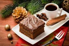 Uma parte de bolo do pão-de-espécie do Natal na placa branca na tabela festiva Imagens de Stock Royalty Free