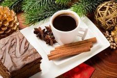 Uma parte de bolo do pão-de-espécie do Natal na placa branca na tabela festiva Imagens de Stock