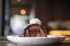 Uma parte de bolo e de chantiliy do rolo do chocolate na parte superior na placa branca da cerâmica na tabela de madeira Foto de Stock Royalty Free