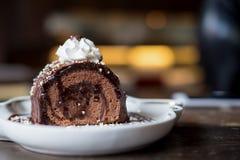 Uma parte de bolo e de chantiliy do rolo do chocolate na parte superior na placa da cerâmica e no copo de café brancos na tabela  Imagens de Stock Royalty Free