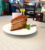 Uma parte de bolo marrom em uma placa branca em uma tabela em uma folha da hortelã do café fotografia de stock royalty free