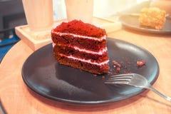 Uma parte de bolo vermelho de veludo em uma placa redonda marrom com forquilhas e Fotografia de Stock Royalty Free