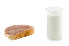 Uma parte de pão e de vidro do leite fotos de stock royalty free