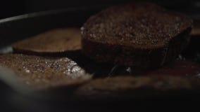 Uma parte de pão escuro cai em uma frigideira com pão cortado filme