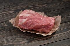 Uma parte de pescoço cru da carne de porco no papel Lombinho de carne de porco no papel em um fundo escuro Fotografia de Stock Royalty Free