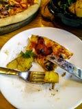 Uma parte de pizza metade-comida em uma placa branca com forquilha e faca Placa de madeira com uma pizza e uma bacia de batatas c fotografia de stock royalty free
