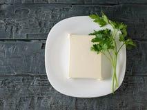 Uma parte de queijo sérvio em uma bacia branca em uma tabela de madeira preta A vista da parte superior Produtos láteos imagem de stock