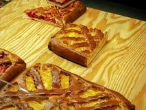 Uma parte de torta do fruto com um amarelo e de enchimento vermelho em uma placa de madeira foto de stock royalty free
