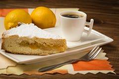 Uma parte de torta do limão e de um copo do chá no fundo de madeira Foto de Stock