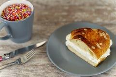 Uma parte do bolo do rei fez à mão no forno, em uma base de madeira acolhedor fotografia de stock royalty free
