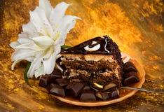 Uma parte do corte de bolo de chocolate em uma placa amarela da pérola com partes de telhas do chocolate em um fundo amarelo de m Fotos de Stock