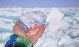 Uma parte do gelo transparente de cristal na mão contra o lago congelado no dia ensolarado fotografia de stock