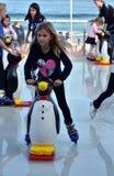 Uma patinagem no gelo da menina com um auxílio do patim do pinguim na pista de gelo de Bondi fotografia de stock royalty free