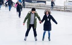 Uma patinagem no gelo dos pares em uma pista exterior em Montreal fotografia de stock