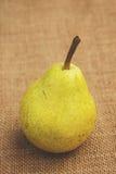 Uma pera amarela que senta-se em uma tabela Fotos de Stock Royalty Free